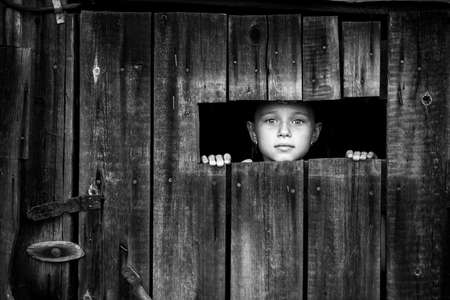 A little girl out peeks anxiously through a crack in the closed door. Black and white photo.