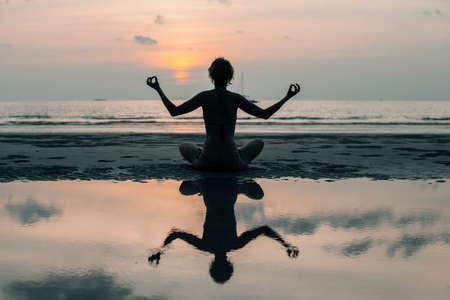 Silhouette of yoga meditation girl on the stunning sea beach at sunset.