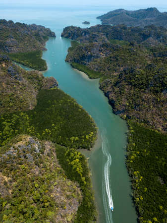 Aerial image of river flowing into the sea. Boat floats on the river. Park Kilim Geoforest Langkawi, Malaysia.