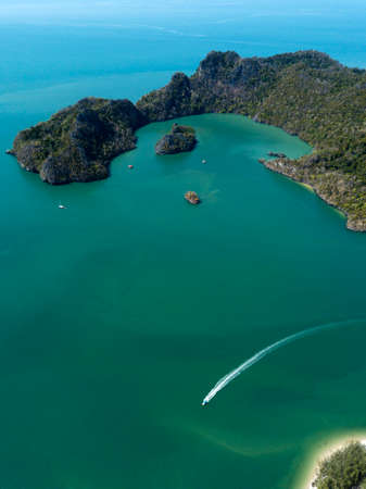 Aerial photo of island in sea. Boat float near the island. Park Kilim Geforest, Langkawi, Malaysia.