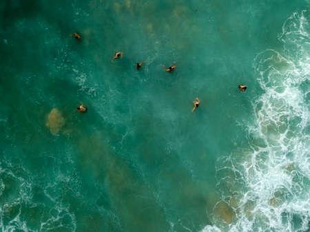 Menschen schwimmen auf den Wellen im Ozean, am Strand von Dreamland. Wellen mit weißem Schaum. Luftbild. Bali, Indonesien.