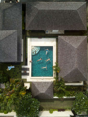 Aerial image of girls swimming in the pool in beautiful villa. Bali, Indonesia.