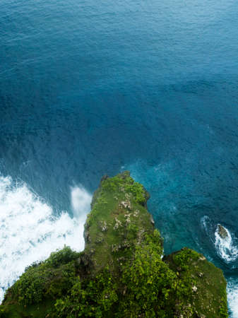 Aerial image of Uluwatu Temple, green cliff and blue ocean with breaking waves in Bali, Indonesia.