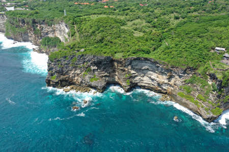 Aerial photo of green cliff and blue ocean with breaking waves in Uluwatu Temple, Bali, Indonesia. 写真素材 - 122433388