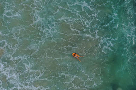 Aerial image of girl swimming on a surfboard in the blue Indian ocean, Dreamland beach, Bali, Indonesia. 写真素材