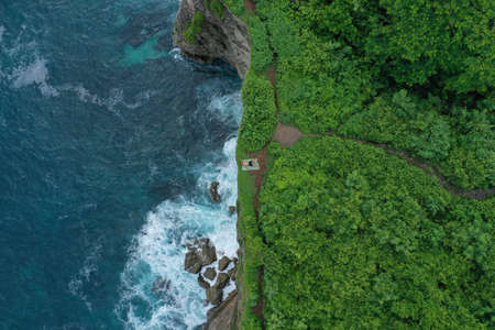 Aerial photo of man lying on a green cliff above the blue Indian Ocean and foaming breaking waves, Uluwatu, Bali, Indonesia. 写真素材 - 122433441