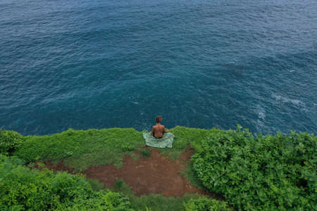 Aerial photo of man sitting on a green cliff edge above the blue Indian Ocean, Uluwatu, Bali, Indonesia. 写真素材 - 122433446