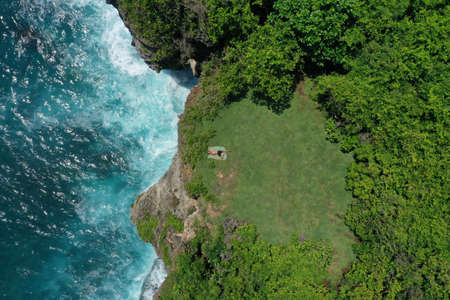 Aerial photo of man lying on a green cliff above the blue Indian Ocean and foaming breaking waves, Uluwatu, Bali, Indonesia.