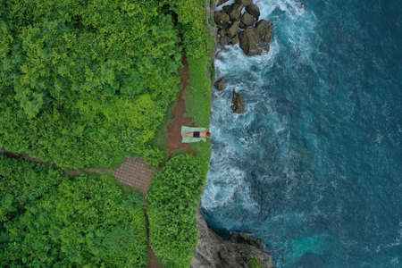 Aerial photo of man lying on a green cliff above the blue Indian Ocean and foaming breaking waves, Uluwatu, Bali, Indonesia. 写真素材 - 122433453
