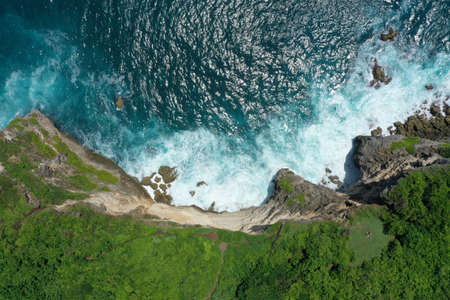 Aerial photo of green cliff and blue ocean with breaking waves in Uluwatu Temple, Bali, Indonesia. 写真素材 - 122433454