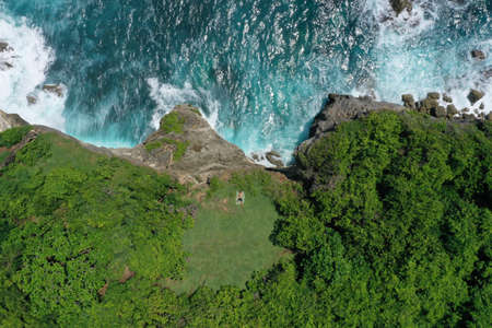 Aerial photo of man lying on a green cliff above the blue Indian Ocean and foaming breaking waves, Uluwatu, Bali, Indonesia. 写真素材 - 122433491