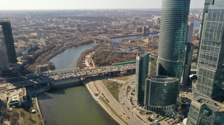 Moscow City from drone in spring sunny day. Bird's eye view. Cars goes on the highway near glass skyscrapers. Russia. Modern life, urbanization.