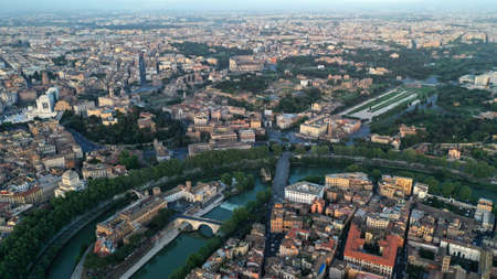 Aerial footage of Tiberina island in Tiber river, Rome, Italy. From drone. Bird's eye view. Sunny day.
