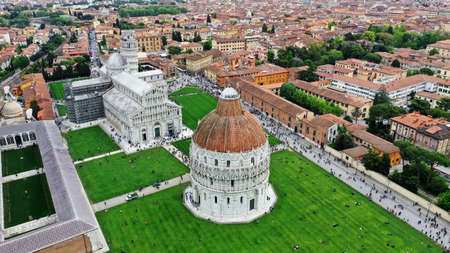 Cathedral of Santa Maria Assunta and Baptistery in Piazza dei Miracoli, Pisa, Tuscany, Italy, Aerial photo from drone. There is pisan houses with orange roofs on the picture. 写真素材