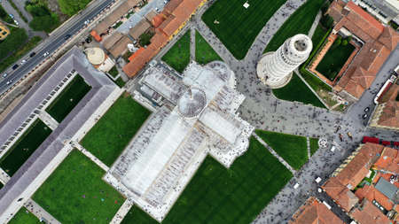Pisa's Leaning Tower in Piazza dei Miracoli, Italy, Tuscany. Aerial photo from drone. There is Cathedral of Santa Maria Assunta and Baptistery on the picture an pisan houses with orange roofs.