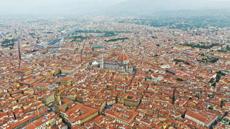 Aerial photo of Santa Maria del Fiore Cathedral in the center of Florence near the Arno River, around the cathedral houses with orange roofs.