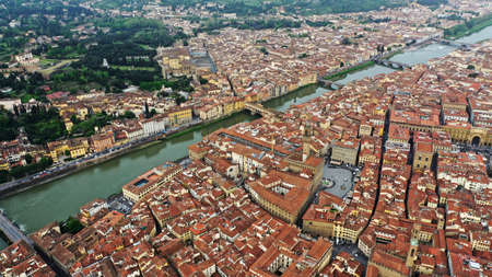 Aerial photo of Arno River and Ponte Vecchio bridge near Cathedral Santa Maria del Fiore in Florence, Italy. Italian orange roofs near the river and cathedral.
