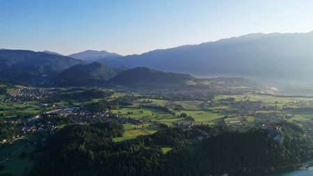Aerial view of Bled Lake valley. Natural landscape with green meadows, fields, hills and mountains, small houses and trees. Sunny blue sky. Sun rays.
