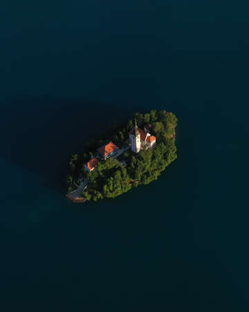 Aerial view of small island with Church of assumption of Mary in the middle of Lake Bled, Slovenia. Summer. Green Mountains landscape around lake. Imagens