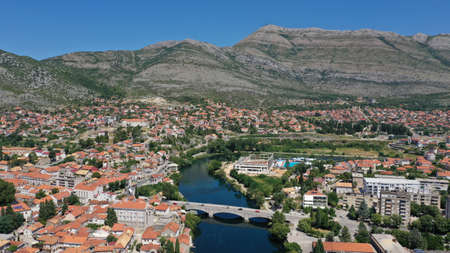 Aerial view of stone bridge (Kameni Most) on Trebisnjica river in Trebinje Old Town. Bosnia and Herzegovina. Summer sunny day, Turquoise water, mountains, trees, blue sky, small houses.