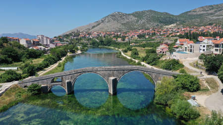 Aerial view of Arslanagic`s bridge on Trebisnjica river in Trebinje Old Town. Bosnia and Herzegovina. Summer sunny day, Turquoise water, mountains, trees, blue sky, small houses. Imagens