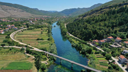 Aerial view of bridge over Trebisnjica river near Lastva village, Bosnia and Herzegovina. Summer sunny day. Turquoise water of river. Mountainous landscape. Green trees and meadows. Balkans.