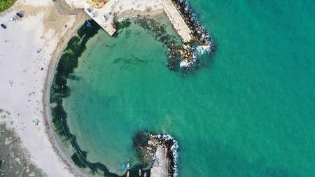 Vue aérienne de haut en bas de Bolata Cove sur la mer Noire, Bulgarie. Plage de sable blanc au bord de la mer près du cap Kaliakra. Des pierres, des vagues écumantes, des gens qui prennent le soleil et des bateaux colorés d'en haut. Banque d'images
