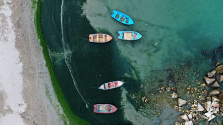 Aerial top down view of colorful fishing boats moored near the shore of Bolata cove on Black sea, Bulgaria. Turquoise water