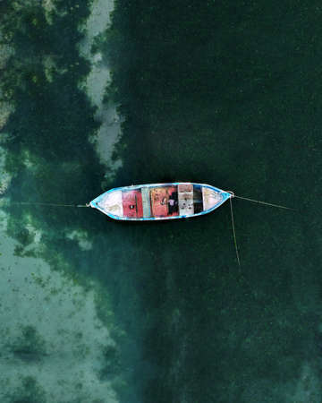 Aerial top down view of one fishing blue boat in sea, moored near shore. Water plants under turquoise water. Bulgaria