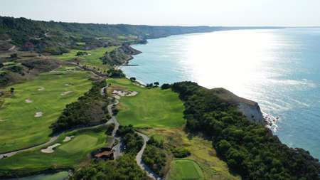 Aerial view of Thracian cliffs golf and beach resort. Beautiful landscape with green hills, meadows, fields for golf, road, hotels and trees near the shore of Black sea, Bulgaria. Summer sunny day. Imagens
