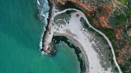 Aerial top down view of Bolata Cove on Black sea, Bulgaria. White sand beach on the sea shore near cape Kaliakra. Stones, foaming waves, sunbathing people and colorful boats from above.