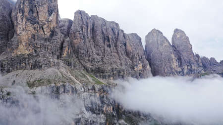 Aerial view of Dolomites Alpine mountains in fog and low clouds. South Tyrol, Italy.