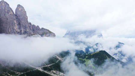 Aerial view of Dolomites in fog, low clouds. Road goes along dolomite cliffs and fir tree forest. South Tyrol, Italy. Beautiful landscape.