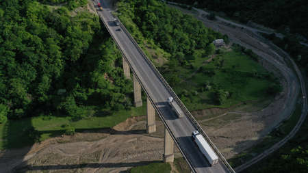 Aerial view of bridge over Aragvi river near Ananuri Fortress and Church. Mountain landscape. Summer. Green trees. Cars going on bridge road. Georgia. Imagens - 138810922