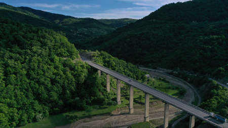 Aerial view of bridge over Aragvi river near Ananuri Fortress and Church. Mountain landscape. Summer. Green trees. Cars going on bridge road. Georgia. Imagens