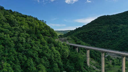 Aerial view of bridge over Aragvi river near Ananuri Fortress and Church. Mountain landscape. Summer. Green trees. Cars going on bridge road. Georgia. Imagens - 138810948