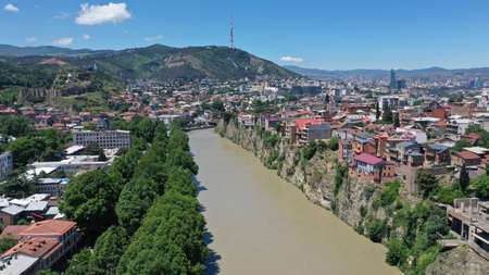 Aerial view of Kura river in Old Town of Tbilisi, Georgia. Church, Houses, trees, mountain ad blue sky. Summer. Travel destinations. Imagens