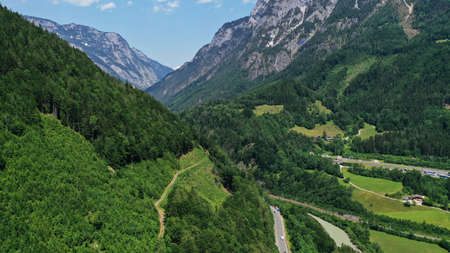 Aerial view of Salzach mountainous valley around Hohenwerfen Castle. Summer landscape with fir-trees, green rocky mountains, blue sky.