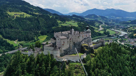 Aerial panoramic view of Hohenwerfen Castle, Austria. Medieval rock fortress in Alpine mountains with spruces. Overlooking the Werfen town in Salzach valley. Summer. Editorial