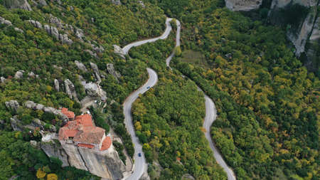 Aerial view of winding road near monastery on the cliff, Meteora mountains valley, Kalampaka, Greece.
