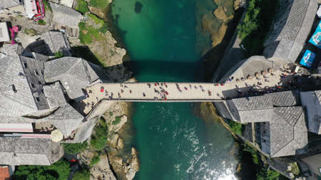 Aerial top down view of old medieval bridge in Mostar, Stari Most, Neretva river, Bosnia and Herzegovina. Sunny summer day. Tourists walking on the bridge. Editorial