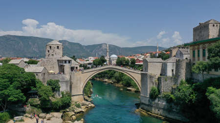 Aerial view of Stari Most old medieval bridge in Mostar, Neretva river, Bosnia and Herzegovina. Tourists walking on the bridge. Summer landscape of old town. Mosque on background.