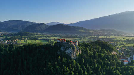 Aerial footage of Bled castle on rocky cliff, Lake Bled in Slovenia, Europe. Natural mountainous landscape around castle, green meadows and fields. Summer.