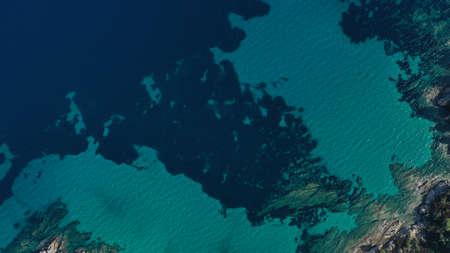 Aerial view of Halkidiki lagoon, Vouvourou beach, turquoise water of Aegean sea, rocks underwater. Greece seascape.