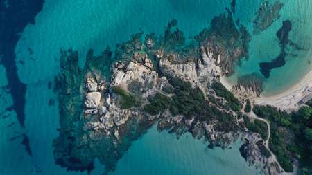 Aerial view of Vourvourou beach, small peninsula in turquoise water of Aegean sea. Waves beating cliff rocky coastline. Halkidiki, Greece. Imagens