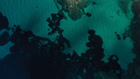 Aerial view of Aegean sea, turquoise water surface, Vourvourou beach, Kavourotripes beach, Sithonia peninsula, Halkidiki, Greece. Rocks, stones underwater.