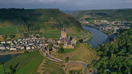 Aerial view of Cochem Castle on the hill near river surrounded by green vineyards, trees, fields, small houses, bridge. German flag waving on the top of tower. Summer. Germany historical landmarks. Editorial
