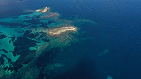 Aerial footage of small islets in turquoise water of Aegean sea, Halkidiki, Sithonia peninsula, Vourvourou beach, Kavourotripes beach, Greece. Beautiful landscape. Small islands. Stones underwater.