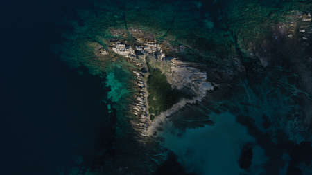 Aerial top down view of small island, islet in turquoise water of Aegean sea. Vourvourou beach, Halkidiki, Greece.