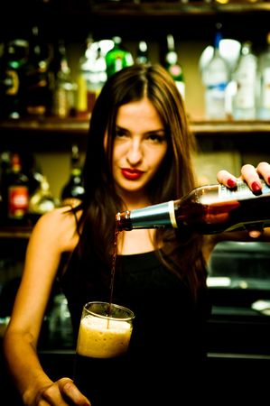 A young female bartender, photographed at work. photo